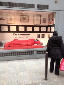 This is art. A live model sleeping in a window vitrine on Rue Dauphine.