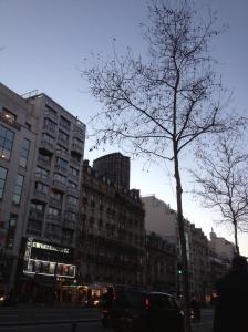 Rue de Montparnasse. Old buildings in the foreground with the Montparnasse Tower in the background.
